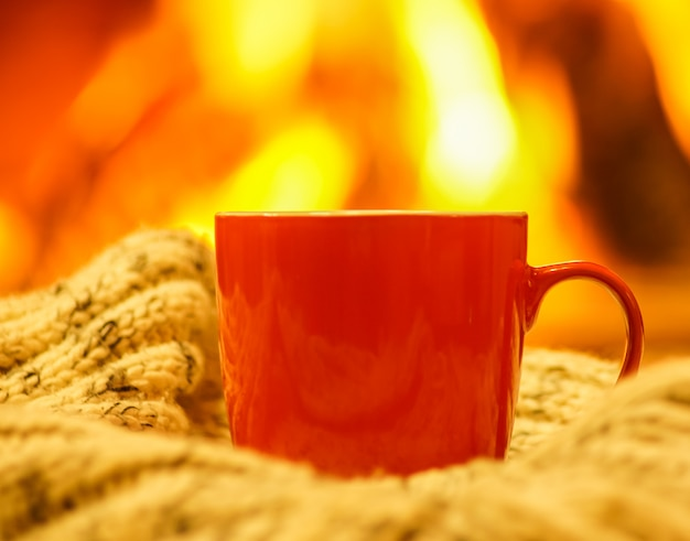Orange mug for tea or coffee, wool things against cozy fireplace background.