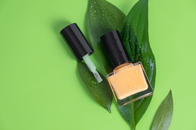 Orange nail polish bottle on green surface.