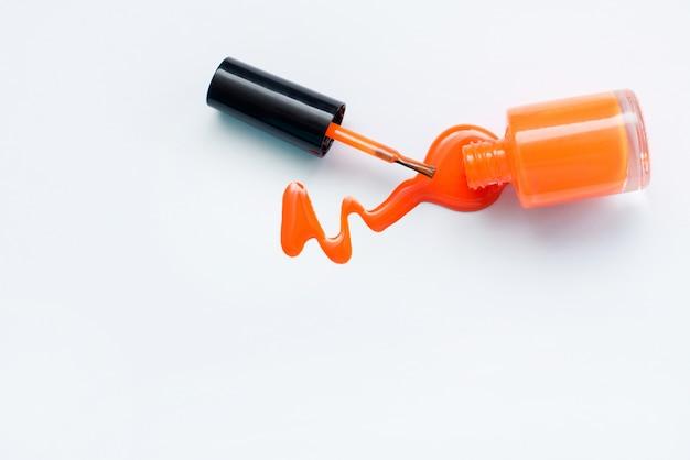 白い背景の上のオレンジ色のマニキュア