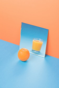 Orange near juice in mirror on blue table isolated
