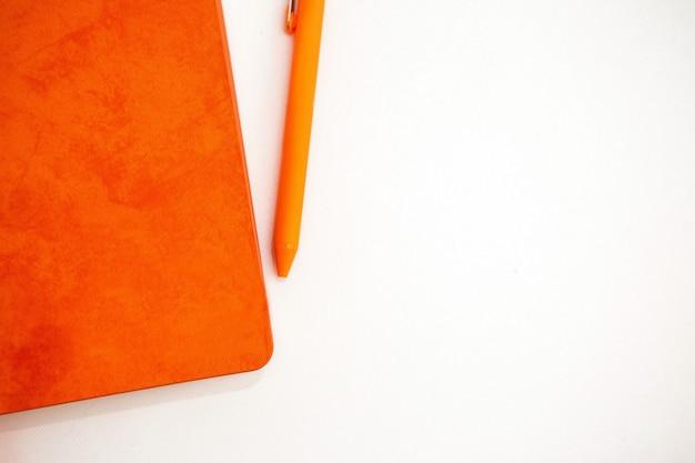 Оранжевый блокнот и шариковая ручка на белом фоне, место для текста