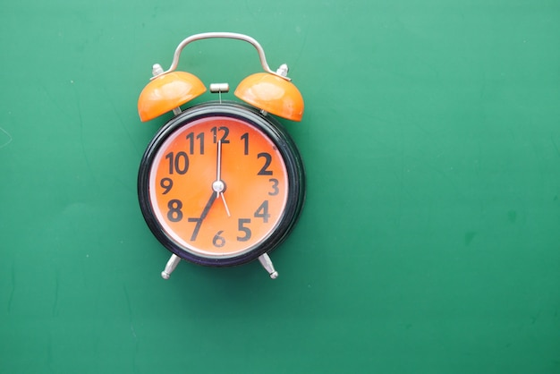 Orange old alarm clock on green background