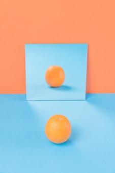 オレンジに分離された青いテーブルの上のオレンジ
