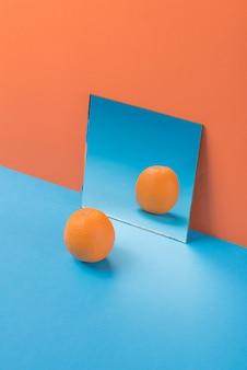 Апельсин на синем столе, изолированные на оранжевый