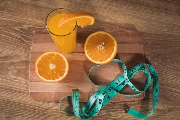 테이블 위의 오렌지, 줄자와 오렌지 주스