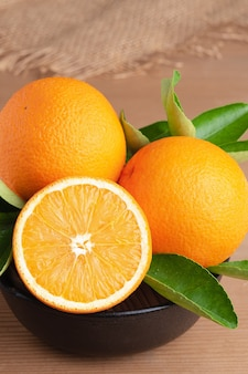 Orange.orange fruits background many orange fruits. oranges group freshly picked in a basket and on a brown wooden table