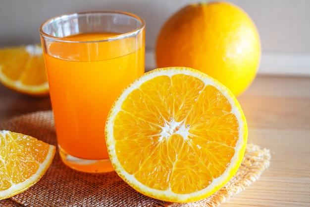Orange and orange juice on wooden background