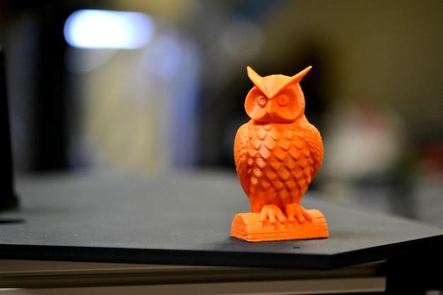 Dプリンターで印刷されたオレンジ色のフクロウオブジェクトは、ぼやけた暗い背景の上に立っています
