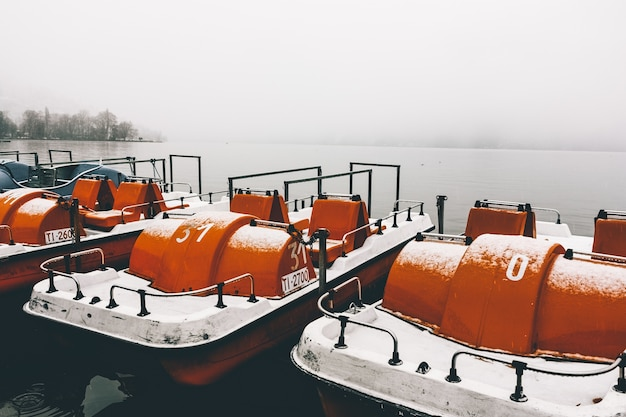 안개가 자욱한 겨울 날에 포착 된 잔잔한 호수의 부두에서 주황색 패들 보트