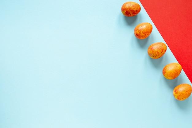 Orange painted eggs aligned on table
