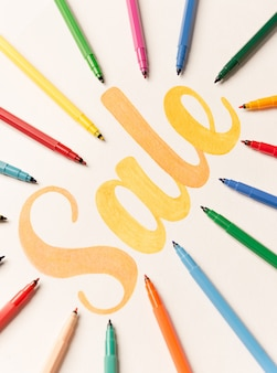 Orange painted lettering sale on white background between markers