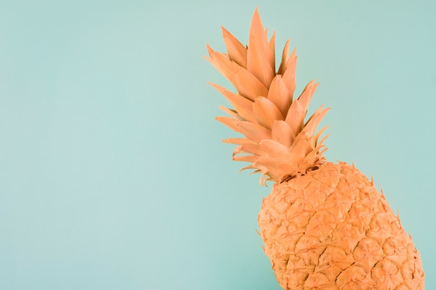 An orange painted pineapple on the corner of blue background