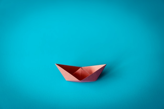 Orange paper boat on blue background with copy space, learning and education concept