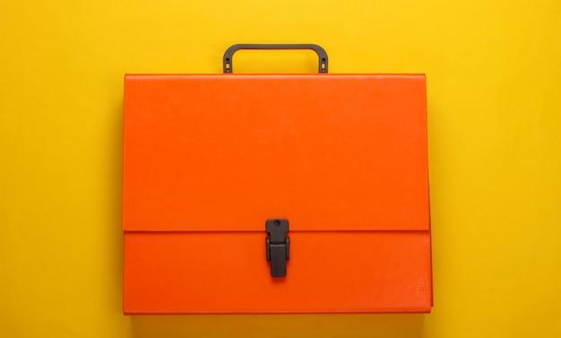 Оранжевый бумажный футляр на желтом.