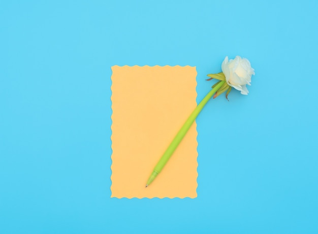 Orange paper sheet with green pen with white flower on it on blue background.