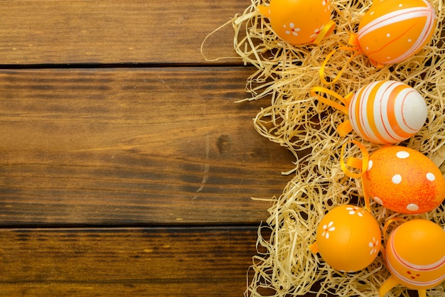 Orange patterned easter eggs in a nest on a brown wooden table. top view, copy space.
