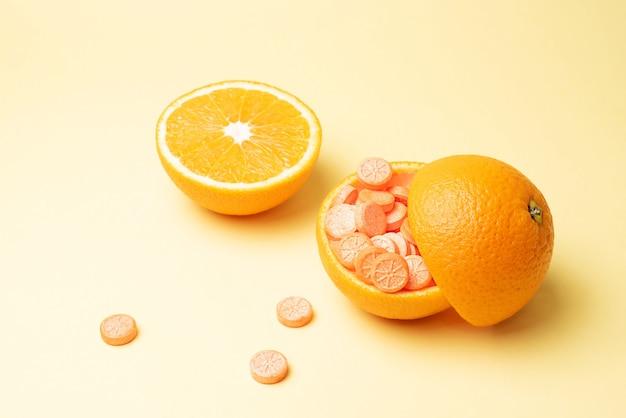 Цедра апельсина, наполненная таблетками витамина с, и половина апельсина на желтом