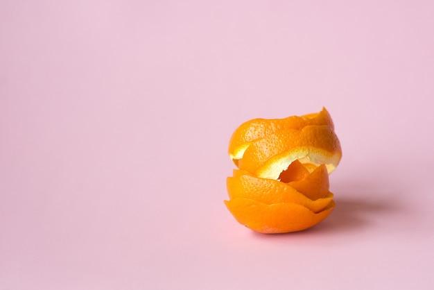リサイクル循環経済のシンボルとしてピンクの背景にオレンジの皮