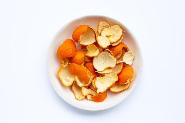 흰색 표면에 접시에 오렌지 껍질