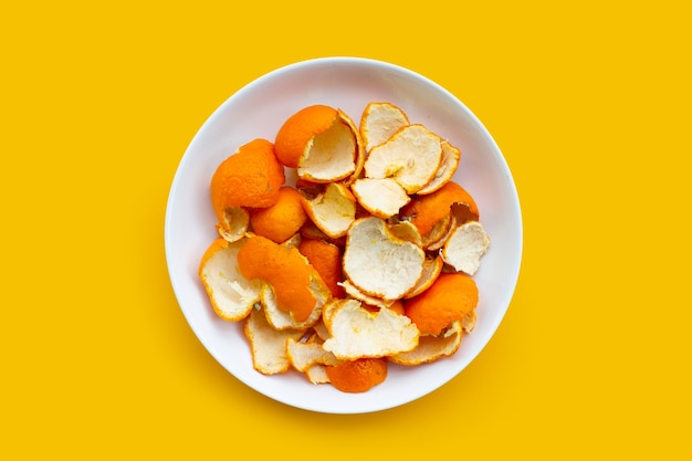 Orange peels in white plate on yellow surface