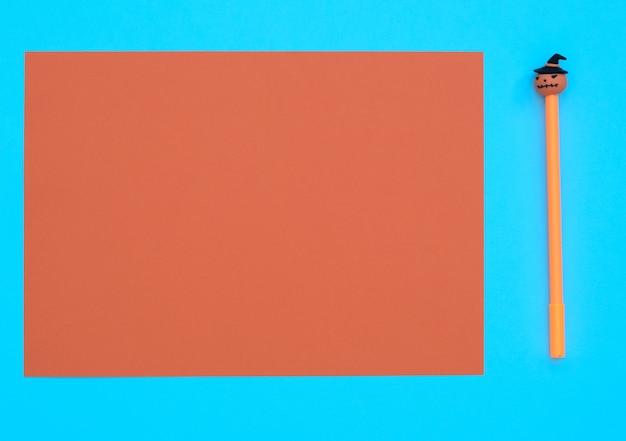 오렌지 시트와 파란색 배경에 장식 호박과 오렌지 펜. 할로윈 개념. 복사 공간이있는 평면 위치 스타일.