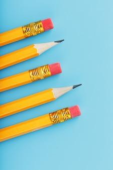 Orange pencils with an eraser on blue.