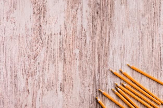 Orange pencils on wooden surface