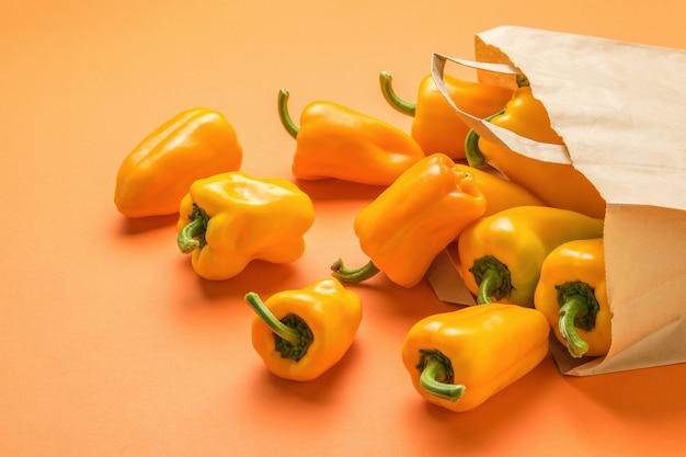 Оранжевый перец высыпается из бумажного пакета на оранжевом фоне. вегетарианская пища.