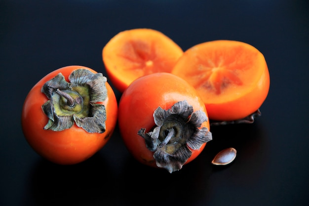 Orange persimmon whole and cut on a black background