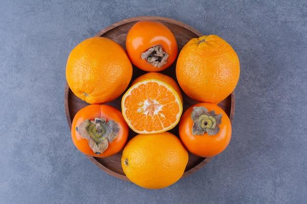 Arancia e cachi sul piatto di legno sulla superficie scura
