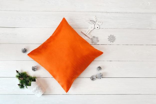 흰색 나무 바탕에 오렌지 베개 케이스 모형입니다. 평면 평신도, 평면도 사진 모형. 휴일 장식.