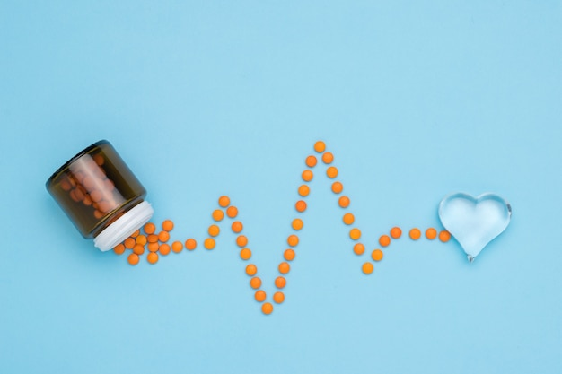 주황색 알약은 유리 병에서 심전도의 형태로 쏟아집니다. 심장 질환 치료의 개념.