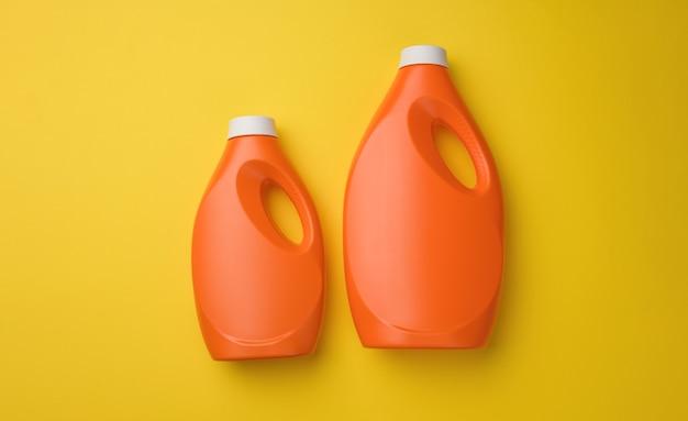 黄色の背景、上面図に液体粉末洗剤用のオレンジ色のプラスチックボトル
