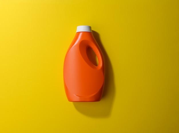 黄色の表面に液体粉末洗剤用のオレンジ色のプラスチックボトル、上面図