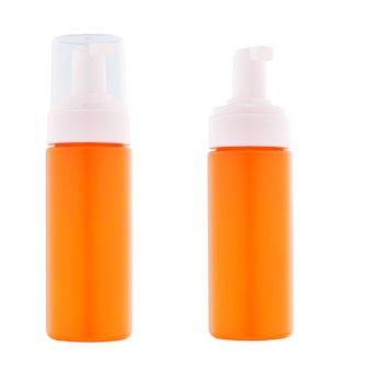 白い背景で隔離のクリームやジェルのオレンジ色のプラスチックディスペンサー。クリーム、スープ、フォーム、その他の化粧品用の蓋付きと蓋なしのディスペンサー。