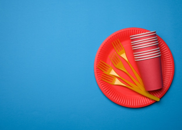 Orange plastic forks and empty red paper disposable plates on a blue background, top view, set
