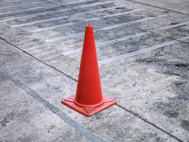 コンクリートの床にオレンジ色のプラスチック製の道路交通コーン