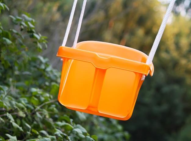 여름 정원의 주황색 플라스틱 그네