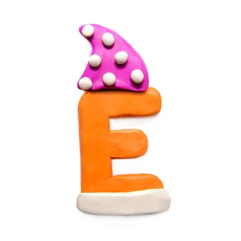 Orange plasticine letter e of the alphabet in a winter pink cap on a white background