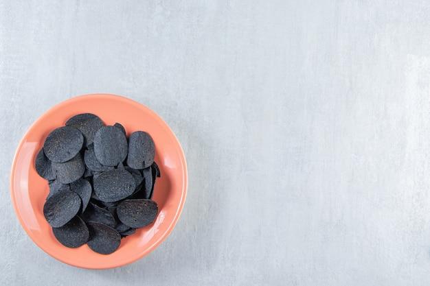 Piatto arancione di patatine croccanti nere su pietra.