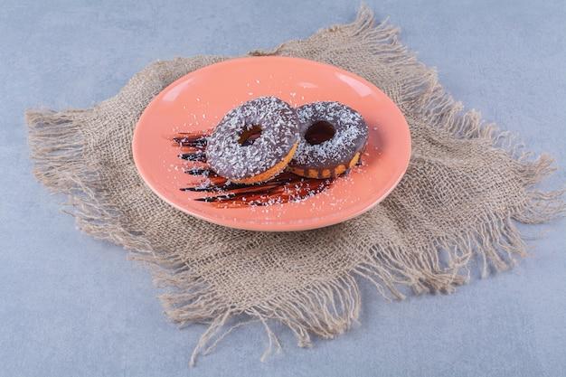 Un piatto arancione di deliziose ciambelle al cioccolato con spruzza su una tela di sacco.