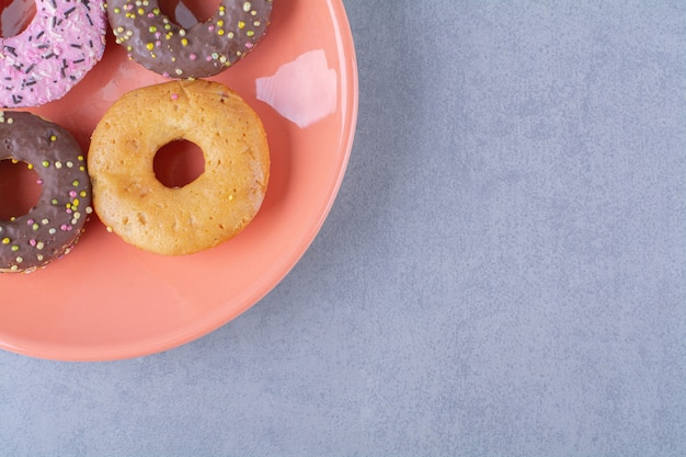 An orange plate of delicious chocolate doughnuts with sprinkles.