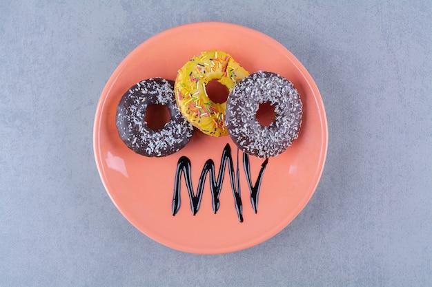 Un piatto arancione di deliziose ciambelle al cioccolato con granelli.