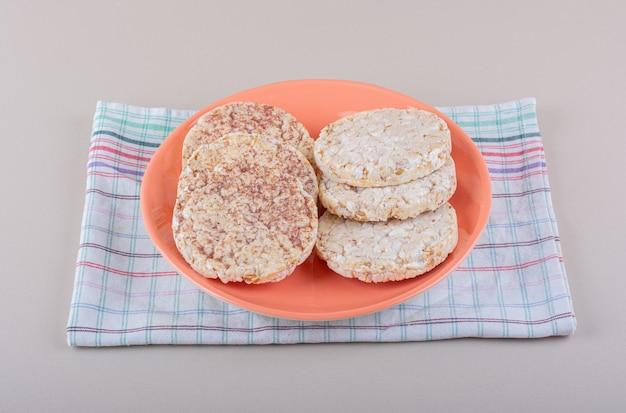 Piatto arancione di deliziose torte di riso sul tavolo bianco. foto di alta qualità