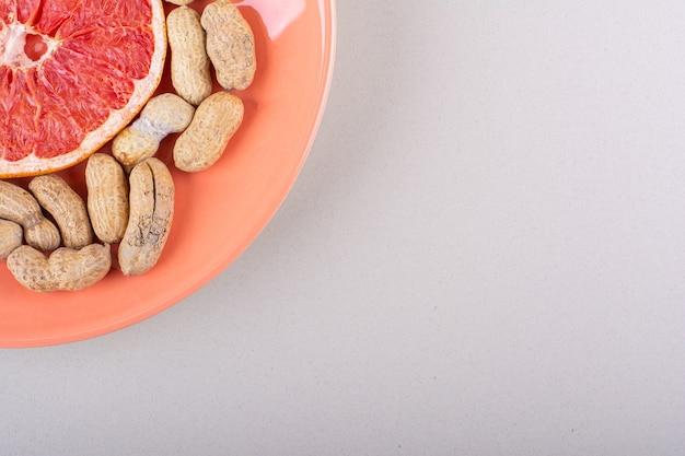 Orange plate of grapefruit slice and organic peanuts on white background. high quality photo