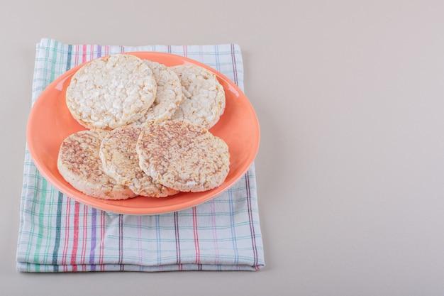 Оранжевая тарелка вкусных рисовых лепешек на белом столе. фото высокого качества
