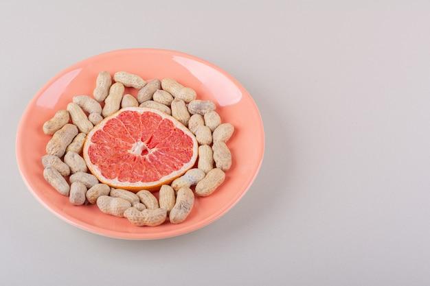 白い背景の上のグレープフルーツスライスと有機ピーナッツのオレンジ色のプレート。高品質の写真