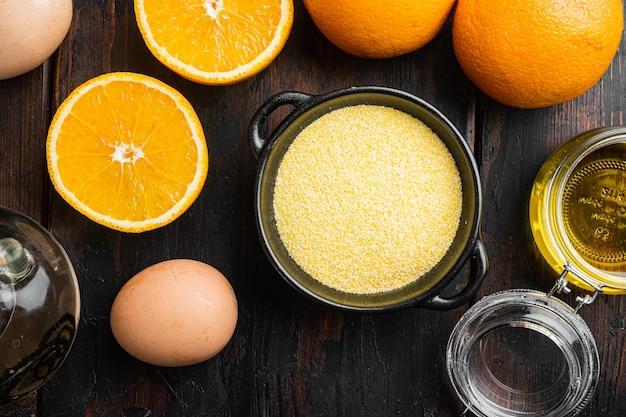 오렌지 폴렌타 케이크 재료, 계란과 꿀 세트, 오래된 짙은 나무 테이블 배경, 평면도