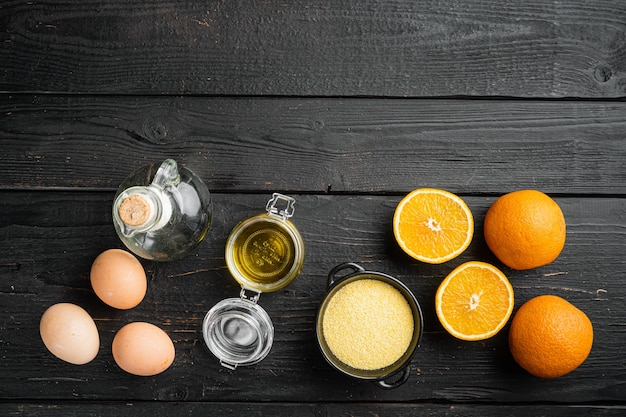 Orange polenta cake ingredients, with eggs and honey set, on black wooden table background, top view flat lay, with copy space for text