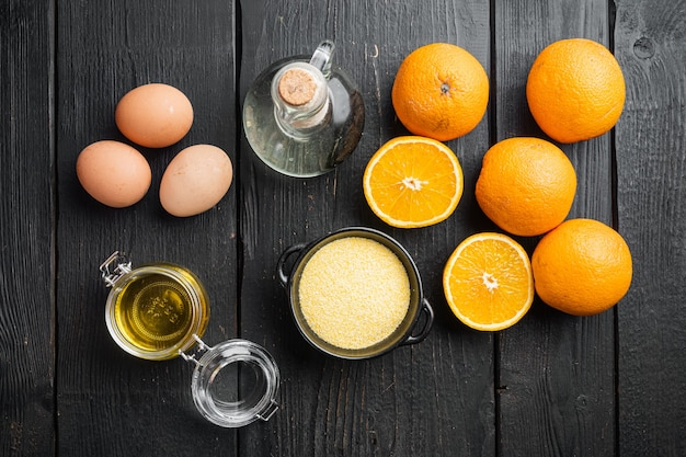 Orange polenta cake ingredients, with eggs and honey set, on black wooden table background, top view flat lay